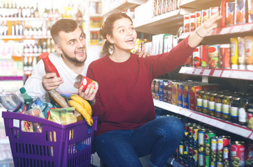 smiling young couple choosing purchasing canned food for week at supermarket