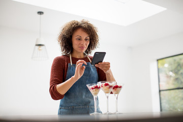 Female food blogger posting a photo with smartphone