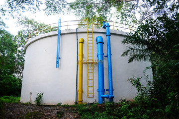 water tank outdoor during raining day with water leaking out from tank background of tropical jungle