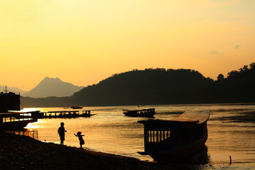 The beautiful sunset and children on the river in Laos
