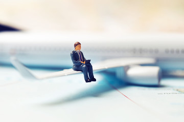 business travel concept - businessman sitting on a plane wing and working with laptop