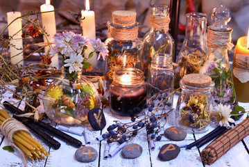 Glass bottles, candles, runes and magic objects on witch table