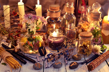 Rune stones, flowers and herbs on witch table in candle light