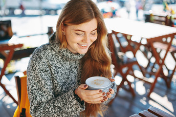 Close-up of reddish natural girl holding a big cup of coffee