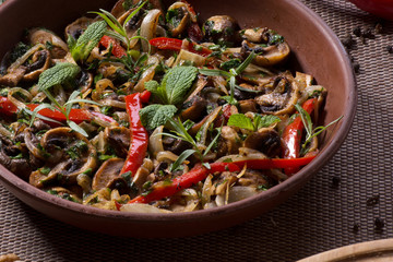 mushrooms with red pepper in a clay dish