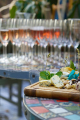 Different kinds of cheeses on wooden board, color table, wineglasses, vertical