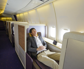 Relaxed mid adult business man sleeping in first class seat