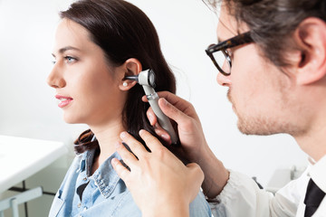 Doctor holding otoscope and Examining a woman patient ear