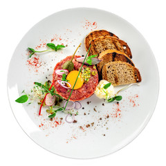 Gourmet tartare, toasted bread and salad on a plate. Delicious healthy French cuisine meal made of raw meat isolated on white background. Top view.