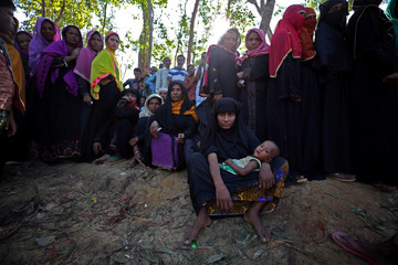 Rohingya refugees line up to receive humanitarian aid in Kutupalong refugee camp near Cox's Bazar