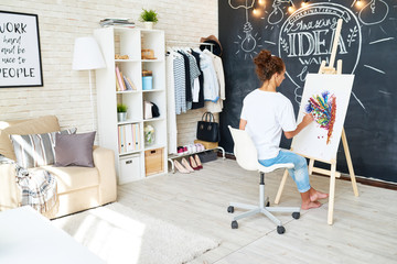 Back view portrait of creative young woman enjoying painting on easel in modern studio apartment