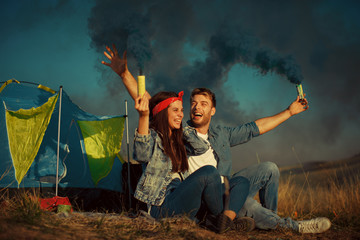 Young happy couple holding smoke bombs on camping