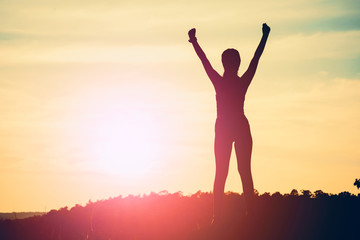 Happy celebrating winning success woman at sunset or sunrise with arms raised up above her head
