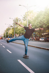 Happy and funny skateboarder ride skateboard through the city street