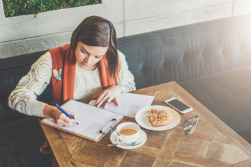 Young businesswoman is sitting in cafe at table, signing documents. Student is studying online, doing homework. Girl is writing letter, statement. On table cup of tea, cookies, smartphone. E-learning.