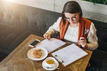 Young businesswoman in glasses and white sweater is sitting in cafe at table,signing documents,working. Student is studying online,doing homework. On table cup of tea, cookies, smartphone. E-learning.