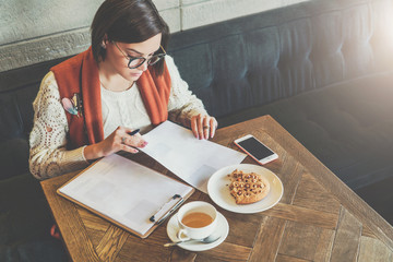 Young businesswoman in glasses and white sweater is sitting in cafe at table,signing documents, working. Girl working online, student doing homework.On table cup of tea,cookies,smartphone. E-learning.