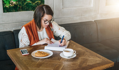 Young businesswoman is sitting in cafe at table,working. Girl fills out an application, questionnaire, signs documents, draws up resume.Student is studying online, doing homework.E-learning,education.