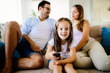 Young girl watching tv with her parents
