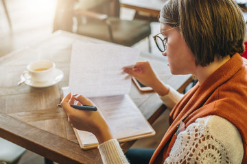 Side view. Young woman sits in cafe at a table, holding pen, reading documents. Online education, marketing. A student does homework. A businesswoman signs a contract. Startup, entrepreneur working.