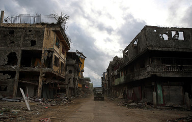 A military truck drives past damaged buildings after government troops cleared the area from pro-Islamic State militant groups inside a war-torn area in Bangolo town, Marawi City