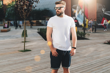 Summer day. Front view. Young bearded hipster man dressed in white t-shirt and sunglasses is stands on city street. Mock up. Space for logo, text, image. Instagram filter, film effect, bokeh effect.
