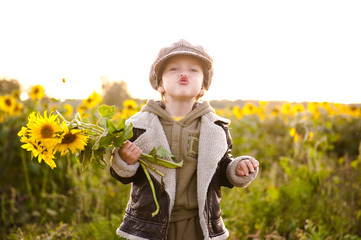 Cheerful little boy in a field of sunflowers.