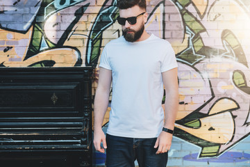 Summer day. Front view. Young bearded hipster man dressed in white t-shirt is stands against wall with graffiti. Mock up. Space for logo, text, image. Instagram filter, film effect.