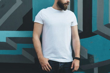 Summer day. Front view. Young bearded hipster man dressed in white t-shirt is stands against wall with graffiti. Mock up. Space for logo, text, image.