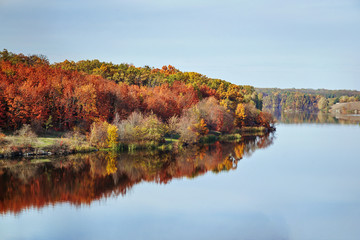 Fall autumn landscape view on the multi colored autumn forest reflecting in the water