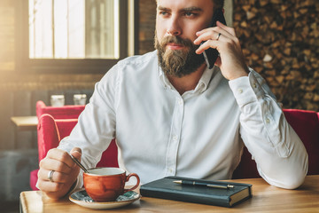 Young bearded businessman sits in cafe at table, drinking tea, talking on cellphone. On table notebook, pen. Man is working, studying.Online education, marketing, training.E-learning,e-commerce.