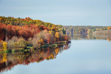 Fall autumn view on the multi colored autumn forest reflecting in the water