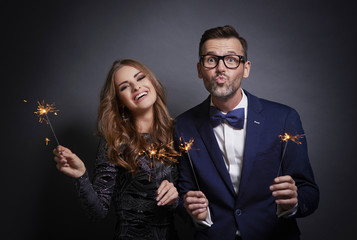 Smart couple with sparklers in studio shot