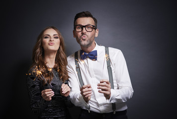 Couple with sparkler making duck face .