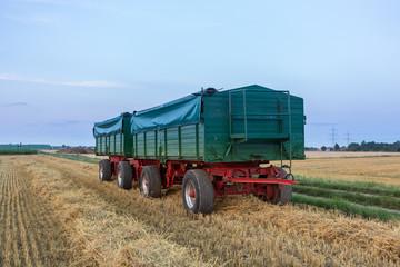 Grüner Landwirtschaftsanhänger abgedeckt mit einer Plane, beladen mit geerntetem Gut im Feld
