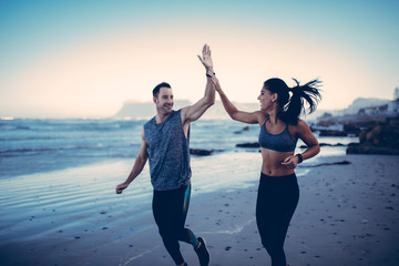 Young adult fitness couple giving high fives to each other