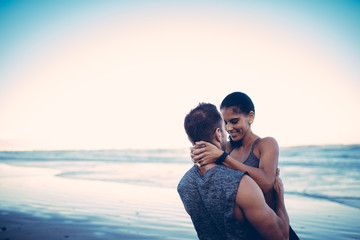 Cute fit couple hugging after workout on beach