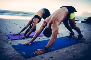 Fit young adult couple doing yoga on beach
