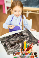 Portrait of adorable little girl painting pictures on Halloween enjoying art lesson in development school