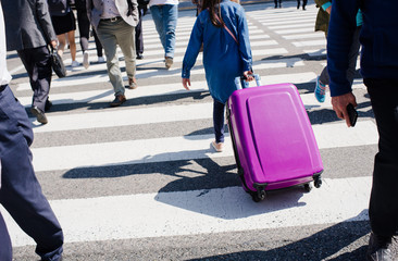 the girl drags a suitcase on wheels on the crosswalk