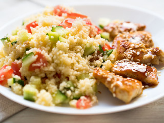 Turkey meat, fried, with teriyaki sauce and sesame seeds. A side dish of Couscous with vegetables. Selective focus, day natural light, side view