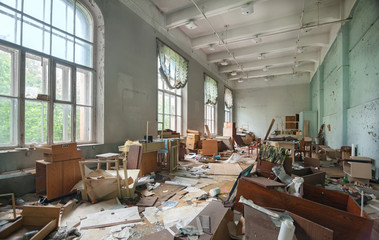 Large room with large vintage windows and broken furniture and trash on the floor. The premise of an old abandoned textile factory