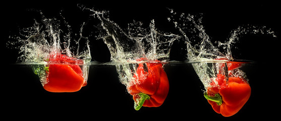 Red bell pepper falling in water