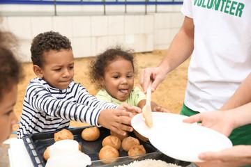 Volunteers sharing food with poor African children outdoors