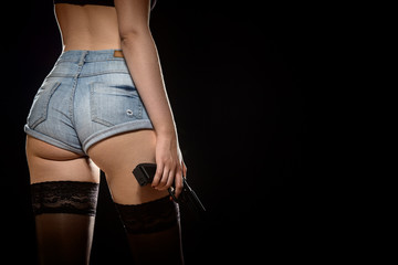 female back in shorts with stockings and gun on black background copy space