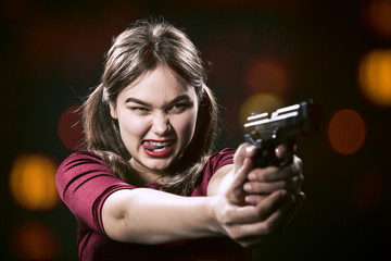fun girl with gun on blurred background aiming at camera, show tongue