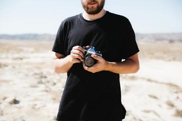 Crop man with camera on desert