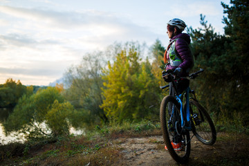 Image of girl with bicycle in helmet in autumn