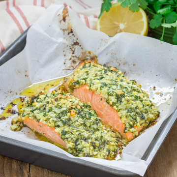 Baked salmon with macadamia cilantro crust in baking dish, square format