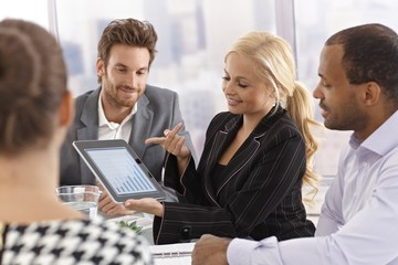 Young businesswoman using tablet at meeting